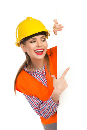 lumberjack shirt: Smiling young woman in yellow hardhat, orange reflective vest and lumberjack shirt standing behind big white banner, holding it, reading and pointing. Waist up studio shot isolated on white. Stock Photo