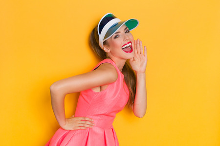 Shouting young woman in pink dress and blue sun visor posing with hand on chin. Three quarter length studio shot on yellow background.