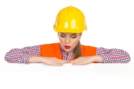 lumberjack shirt: Surprised young woman in yellow hardhat, orange reflective vest and lumberjack shirt posing behind big white poster and looking down. Studio shot isolated on white.