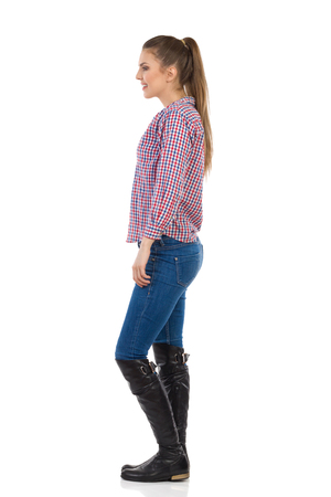Glimlachende jonge vrouw met paardenstaart staand in jeans, zwarte laarzen en houthakker shirt. Zijaanzicht. Full length studio shot geïsoleerd op wit.