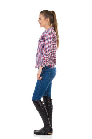 persona de pie: mujer joven con cola de caballo de pie en vaqueros, botas negras y camisa de le�ador sonriendo. Vista lateral. Estudio de longitud completa aislado disparo en blanco.