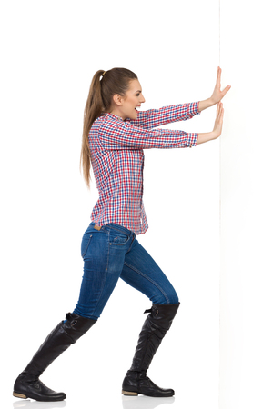 lumberjack shirt: Smiling young woman in jeans, black boots and lumberjack shirt pushing a white wall. Side view, full length studio shot isolated on white. Stock Photo