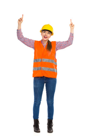 lumberjack shirt: Smiling young woman in yellow hardhat, orange reflective vest, lumberjack shirt, jeans and black boots, raising arms, looking up and pointing. Full length studio shot isolated on white.