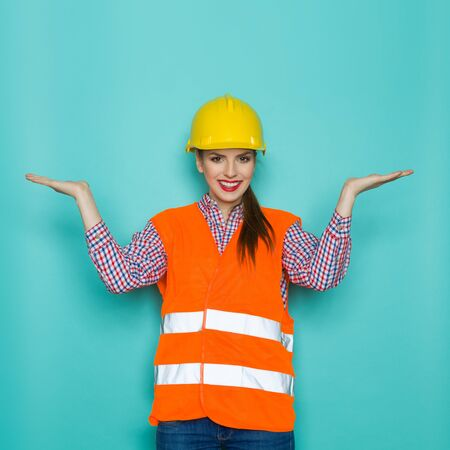 lumberjack shirt: Smiling young woman in orange reflective vest, yellow hardhat, lumberjack shirt and jeans posing with open raised open hands and looking at camera. Three quarter length studio shot on turquoise background.