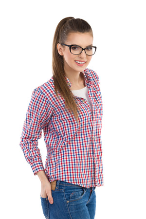 lumberjack shirt: Young woman in glasses and lumberjack shirt posing and holding hand in back pocket. Three quarter length length studio shot isolated on white.