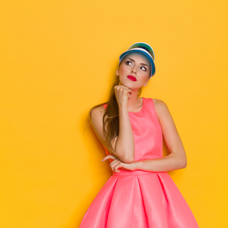 inventing: Young woman in pink dress and blue sun visor posing with hand on chin and looking up. Three quarter length studio shot on yellow background.