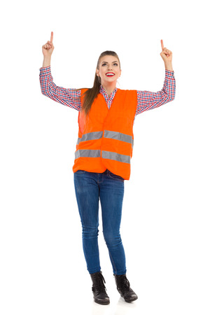 lumberjack shirt: Smiling young woman in orange reflective vest, lumberjack shirt, jeans and black boots, looking up, raising arms and pointing. Full length studio shot isolated on white. Stock Photo