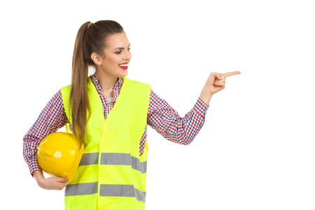 green clothes: Cheerful young woman in reflective vest holding hardhat under her arm looking away and pointing. Waist up studio shot isolated on white.