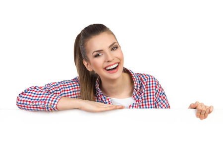 leans: Laughing beautiful young woman in lumberjack shirt leans on a white banner and looking at camera. Head and shoulders studio shot isolated on white.