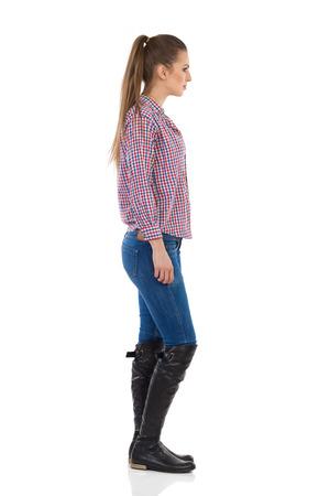 Jonge vrouw in jeans, zwarte laarzen en houthakker shirt. Zijaanzicht. Full length studio shot geïsoleerd op wit.