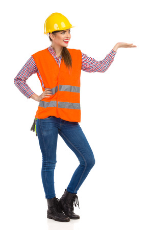 lumberjack shirt: Smiling young woman in yellow hardhat, orange reflective vest, lumberjack shirt, jeans and black boots, posing with open raised hand and looking away. Full length studio shot isolated on white.