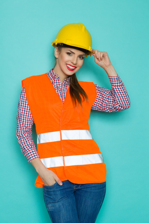 reflective vest: Smiling young woman in orange reflective vest, yellow hardhat and jeans posing with hand in pocket. Three quarter length studio shot on turquoise background. Stock Photo
