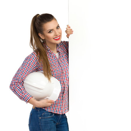 lumberjack shirt: Smiling beautiful young woman in lumberjack shirt standing close to big banner and holding white hardhat under her arm. Waist up studio shot isolated on white.