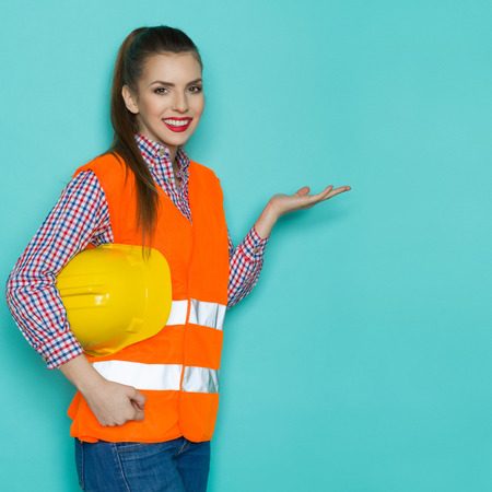 reflective: Smiling young woman in orange reflective vest, lumberjack shirt and jeans holding yellow hardhat under the arm and posing with open hand. Three quarter length studio shot on turquoise background.
