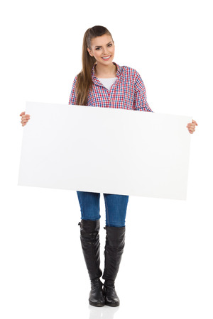 lumberjack shirt: Smiling young woman in jeans, black boots and lumberjack shirt standing and holding white placard. Full length studio shot isolated on white.