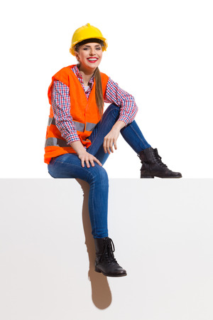 reflective: Smiling young woman in orange reflective vest, yellow hardhat, lumberjack shirt, jeans, black boots, sitting on top in the sunlight. Full length studio shot isolated on white. Stock Photo