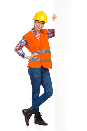 reflective vest: Smiling young woman in yellow hardhat, orange reflective vest and lumberjack shirt posing with big banner. Full length studio shot isolated on white.