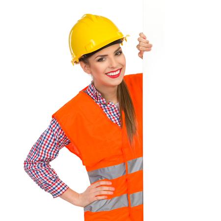 lumberjack shirt: Smiling young woman in yellow hardhat, orange reflective vest and lumberjack shirt posing with big banner. Waist up studio shot isolated on white. Stock Photo