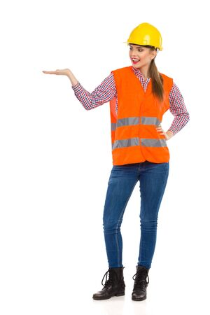 reflective vest: Young woman in orange reflective vest and yellow hardhat holding hand raised and presenting. Full length studio shot isolated on white. Stock Photo