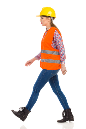 lumberjack shirt: Young woman in orange reflective vest, yellow hardhat, lumberjack shirt, jeans, black boots, walking and looking away. Side view. Full length studio shot isolated on white.