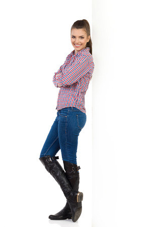 lumberjack shirt: Young woman in jeans, black boots and lumberjack shirt leans with arms crossed on white wall and looking at camera. Side view. Full length studio shot isolated on white.