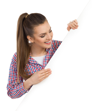 lumberjack shirt: Smiling beautiful young woman in lumberjack shirt peekieng behind white banner and reading. Head and shoulders studio shot isolated on white.