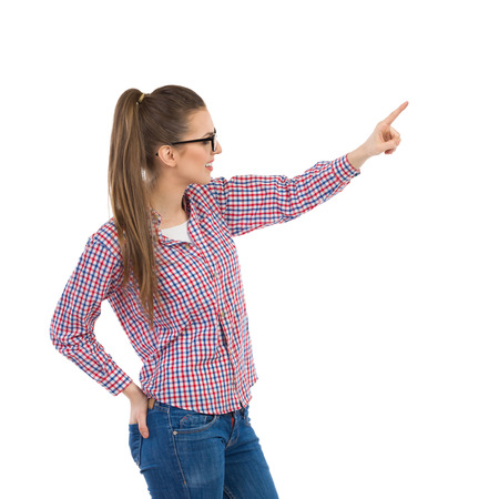 lumberjack shirt: Smiling young woman in glasses wearing lumberjack shirt and jeans pointing and looking away. Three quarter length studio shot isolated on white.