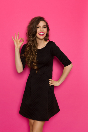 Smiling elegance woman in black mini dress standing and showing ok sign. Three quarter length studio shot on pink background.