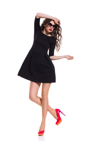 Beautiful woman in sunglasses wearing black mini dress and red high heels posing on one leg. Full length studio shot isolated on white.