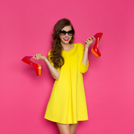 woman red dress: Smiling young woman in yellow mini dress and sunglasses holding two red high heels. Three quarter length studio on pink background.