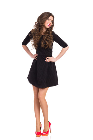 Beautiful young woman in black mini dress and red high heels posing with hands on hip and looking away. Full length studio shot isolated on white.