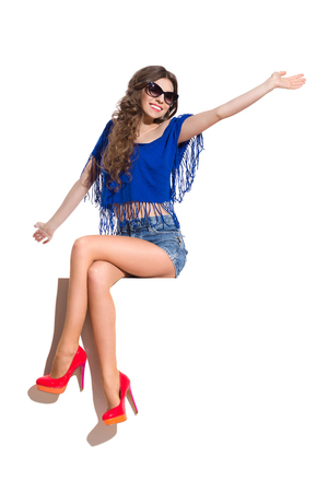 legs crossed at knee: Smiling young woman in sunglasses, blue top, jeans shorts and red high heels sitting at the white banner with legs crossed at knee and waving hand. Full length studio shot isolated on white. Stock Photo
