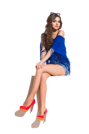legs crossed at knee: Young woman in blue top, jeans shorts and red high heels sitting at the top of white banner with legs crossed at knee and looking at camera. Full length studio shot isolated on white. Stock Photo