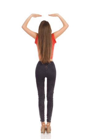 arms above head: Rear view of young girl standing in red top, black jeans and high heels with arms raised holding something above her head. Full length studio shot isolated on white.