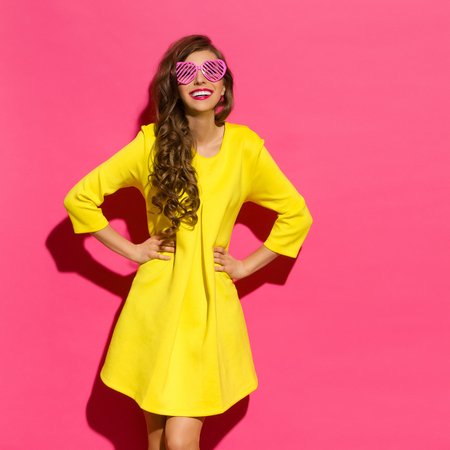 Beautiful young woman in yellow mini dress and pink heart shaped sunglasses posing with hands on hip. Three quarter length studio shot on pink background. Standard-Bild