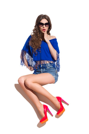 adult oops: Surprised sexy woman in sunglasses, blue top, jeans shorts and red high heels sitting on the white banner and holding hand on chin. Full length studio shot isolated on white.