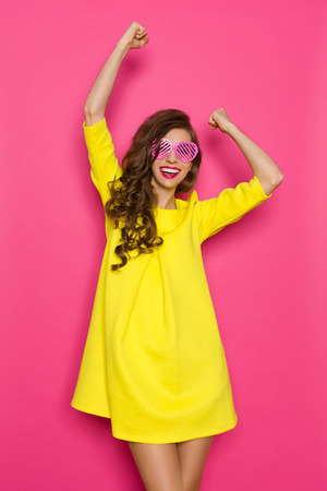 Beautiful young woman in yellow mini dress and pink heart shaped sunglasses posing with arms raised. Three quarter length studio shot on pink background.