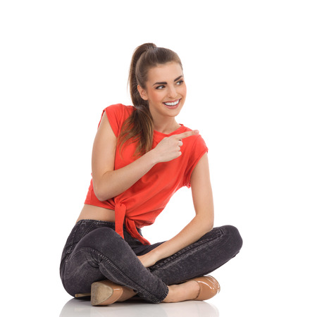 Beautiful smiling girl in red top, black jeans is sitting on the floor with legs crossed, pointing and looking away. Full length studio shot isolated on white. Stock Photo