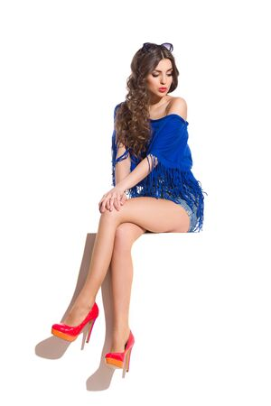 legs crossed at knee: Curious young woman in blue top, jeans shorts and red high heels sitting at the top of white banner with legs crossed at knee and looking down. Full length studio shot isolated on white. Stock Photo