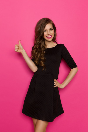 Smiling elegance young woman in black mini dress posing with hand on hip and showing thumb up. Three quarter length studio shot on pink background.
