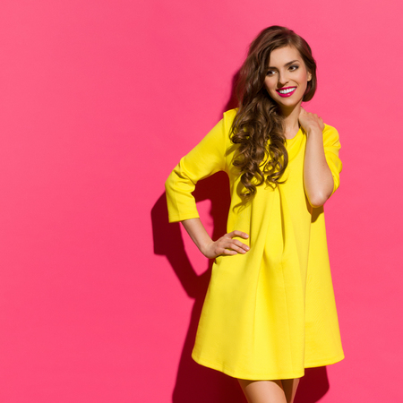 Smiling young woman in yellow mini dress posing against pink background and looking away at copy space. Three quarter length studio shot. Stockfoto