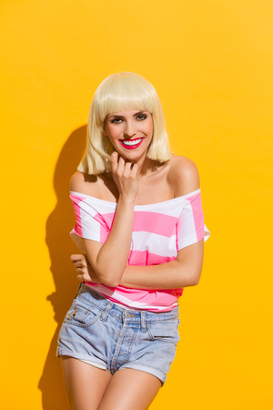 three quarter length: Smiling beautiful blond young woman. Three quarter length studio shot on yellow background.
