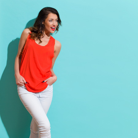 three quarter length: Young woman in jeans and red shirt holding hands in pockets, shouting and looking away. Three quarter length studio shot on teal background.