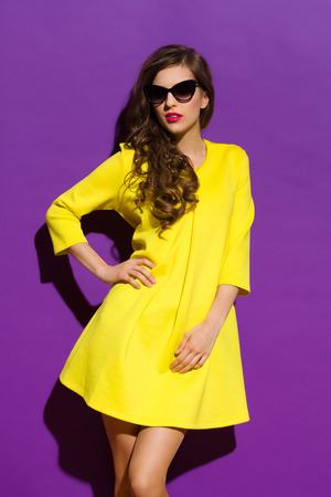 specs: Beautiful girl in sunglasses posing in yellow mini dress. Three quarter length studio shot on violet background.