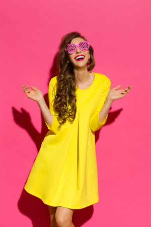 Beautiful young woman in yellow mini dress and pink heart shaped sunglasses posing with arms outstretched. Three quarter length studio shot on pink background. Standard-Bild