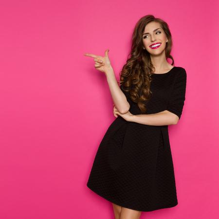 Lachende elegantie vrouw in zwarte mini jurk staan, wijzend en wegkijken. Drie kwart lengte studio geschoten op roze achtergrond.