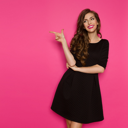 Smiling elegance woman in black mini dress standing, pointing and looking away. Three quarter length studio shot on pink background.