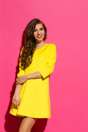 three quarter: Smiling young woman in yellow mini dress posing against pink background. Three quarter length studio shot. Stock Photo
