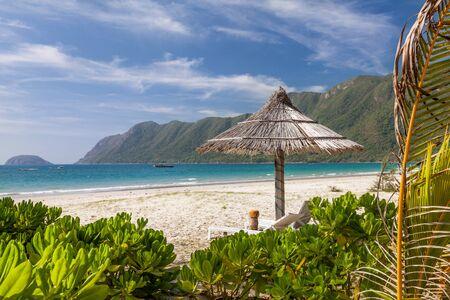 ベトナムで Con dao コンダオ島の熱帯のビーチでの孤独なわら傘