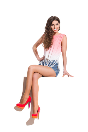 legs crossed at knee: Smiling sexy woman in pink top, jeans shorts and red high heels sitting on the white banner. Full length studio shot isolated on white. Stock Photo